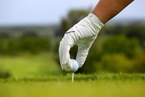 A hand teeing up a ball