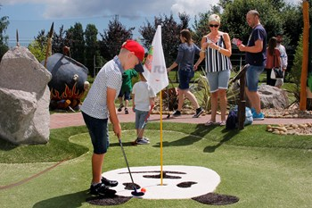 Child playing golf with parents